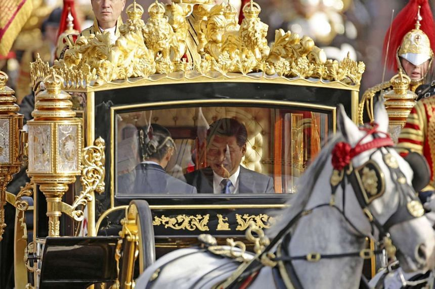 Britain's Queen Elizabeth and the President of China, Xi Jinping (R), are driven by carriage along The Mall to Buckingham Palace.