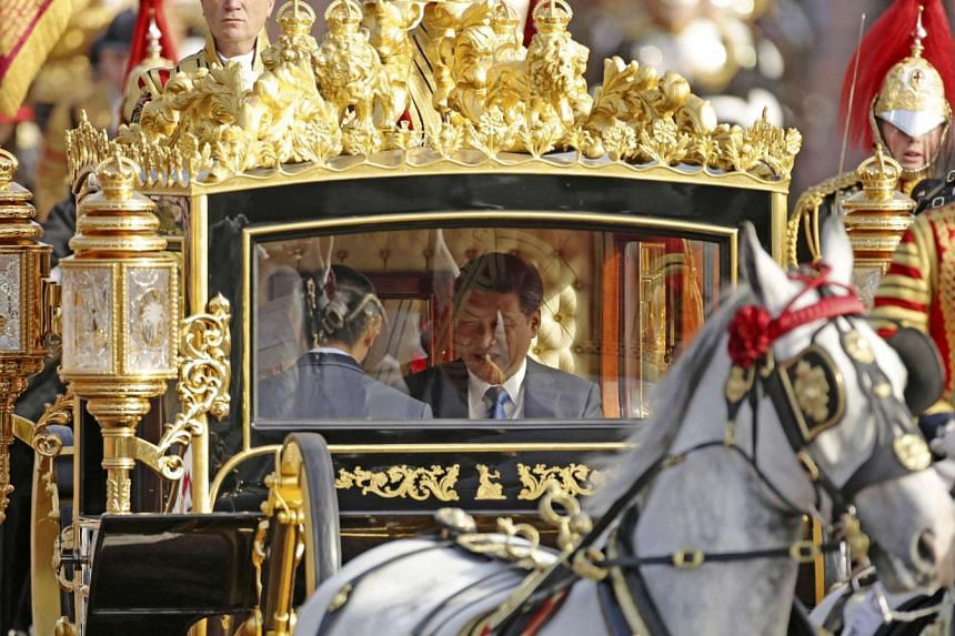 Britain's Queen Elizabeth and Chinese President Xi Jinping (right) are driven by carriage along The Mall to Buckingham Palace in London during his visit to Britain.