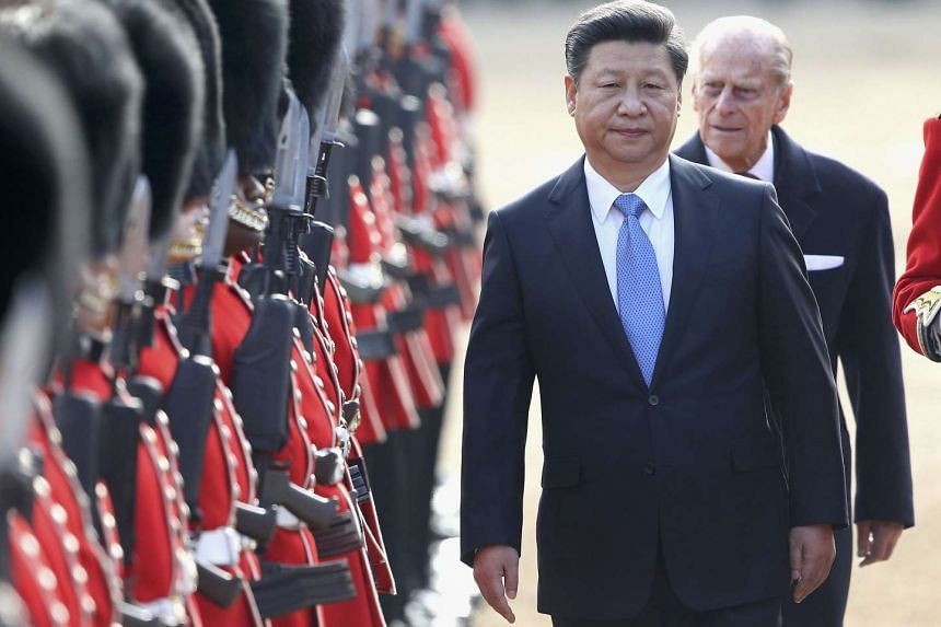 China's President Xi Jinping and Britain's Prince Philip review an honour guard during his official welcoming ceremony in London.