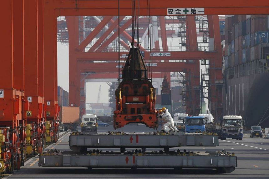 Workers pushing a crane at a port in Tokyo on Oct 20.