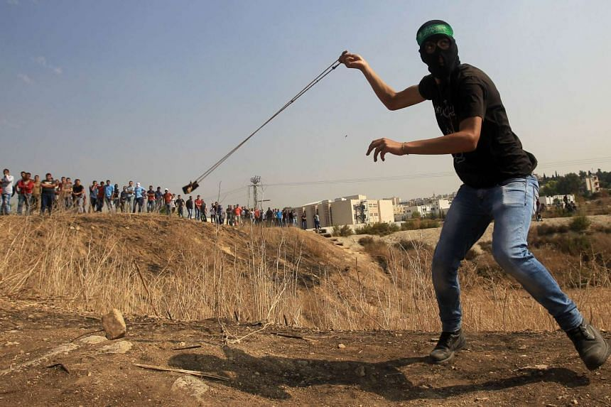 A masked Palestinian protester uses a slingshot to throw stones towards Israeli security forces during clashes in the West Bank town of Tulkarem on Tuesday.