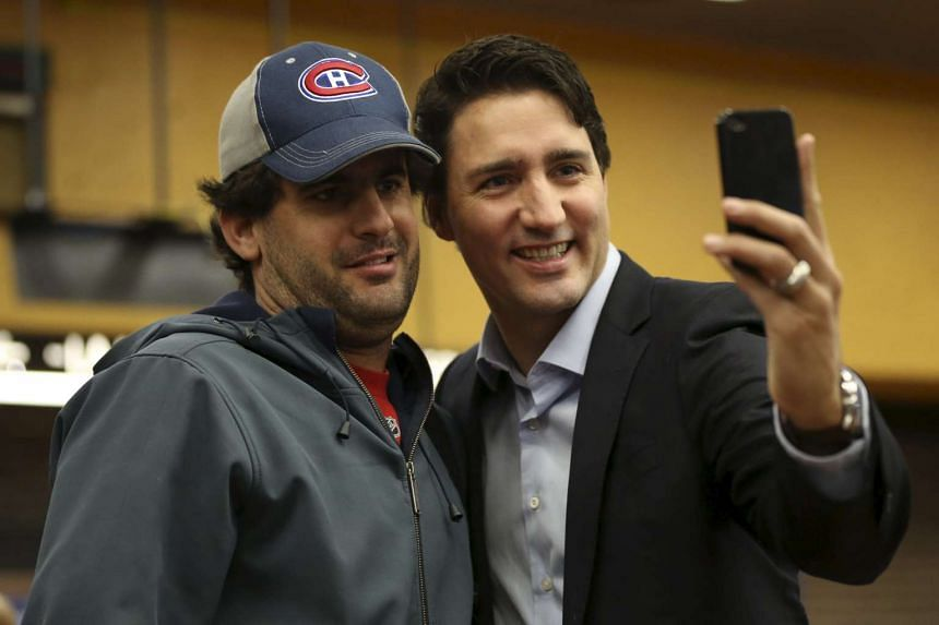 Liberal leader and prime minister-designate Justin Trudeau takes a selfie while greeting people at a subway station in Montreal, Quebec, on Tuesday.