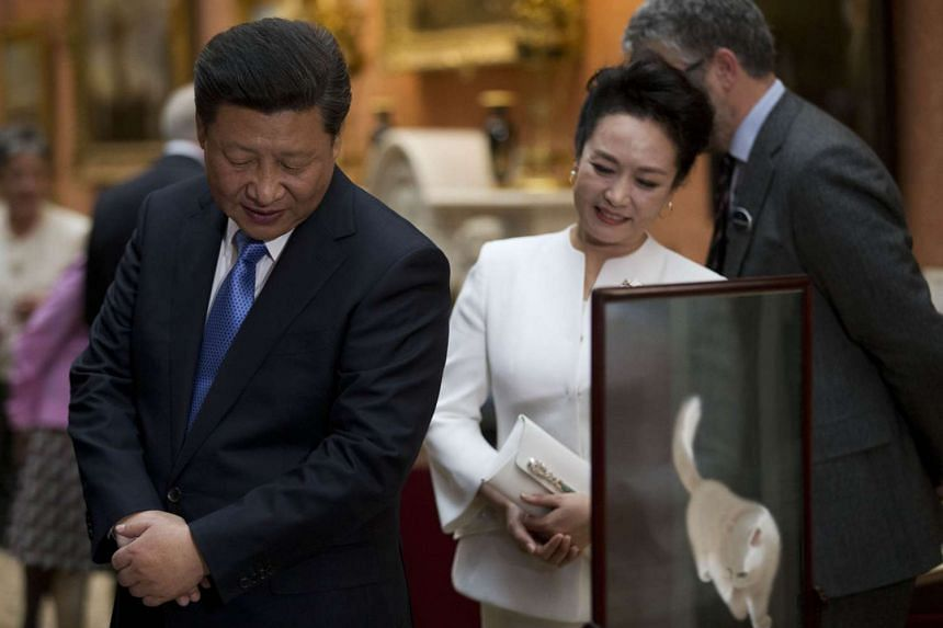 Chinese President Xi Jinping and his wife Peng Liyuan view a display of items related to China in the Royal Collection at Buckingham Palace in London on Tuesday, the first full day of his four-day state visit.