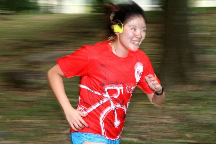 ST reporter Lisabel Ting trying out sports headphones by running and doing cartwheels. Sports headphones and earphones differ from regular ones as they are 