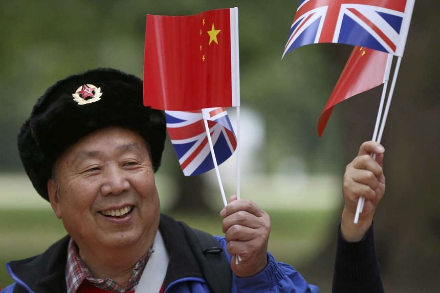 A supporter of China's President Xi Jinping waits on the Mall for him to pass during his ceremonial welcome.
