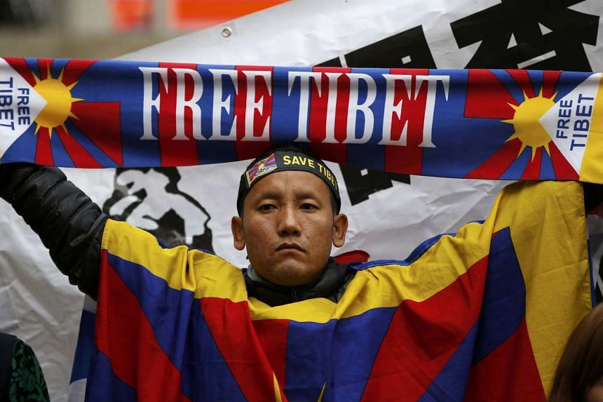 A pro-Tibet protester holds upa scarf as he waits for China's President Xi Jinping to pass on the Mall during his ceremonial welcome.