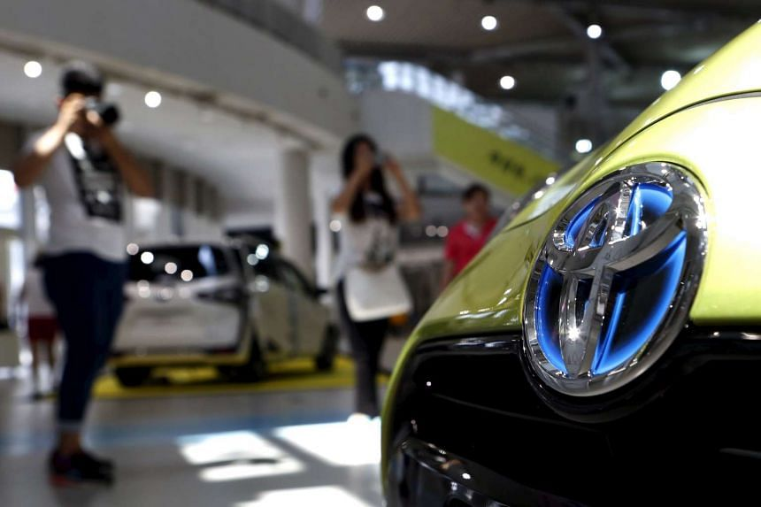 Visitors taking pictures of Toyota Motor Corp's cars displayed at the company's showroom in Tokyo, Japan, on Aug 4, 2015.