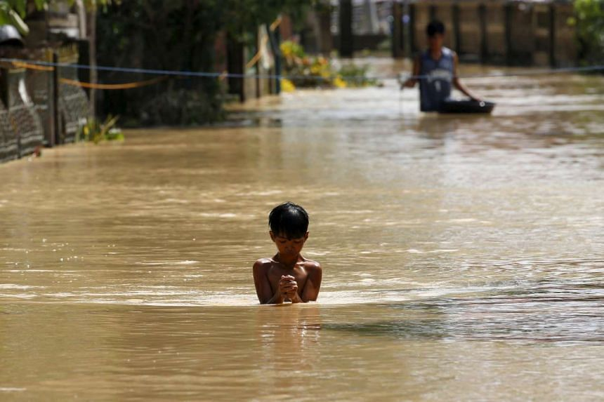 A boy wades through a flooded street in Jaen, Nueva Ecija in northern Philippines on Oct 20, 2015, after the province was hit by Typhoon Koppu.