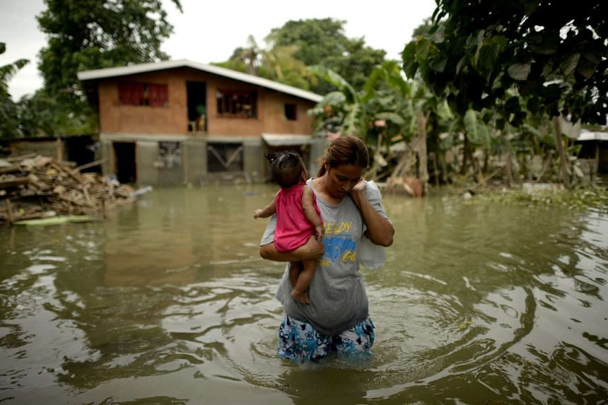 Levelyn Alcoriza leaves her flood submerged house to evacuate to Balzain Elementary School in Macapagal, north of Manila on Oct 21, 2015.