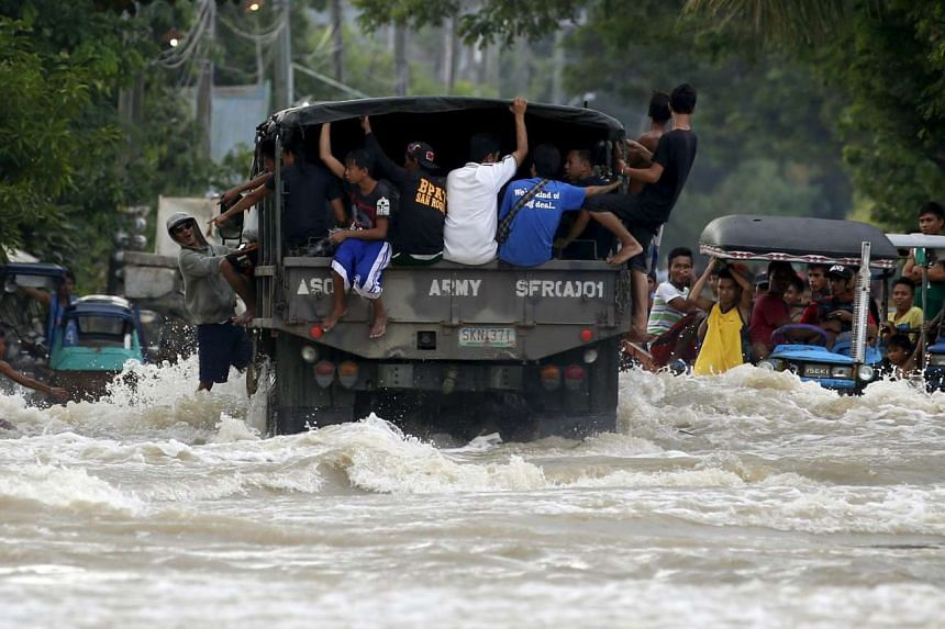 Typhoon victims are transported on a military truck along a flooded portion of a highway in Zaragoza, northern Philippines on Oct 20, 2015.