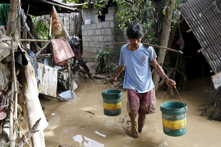 A resident carries water containers as he wades through muddy floodwaters in Cabanatuan city, northern Philippines on Oct 20, 2015.