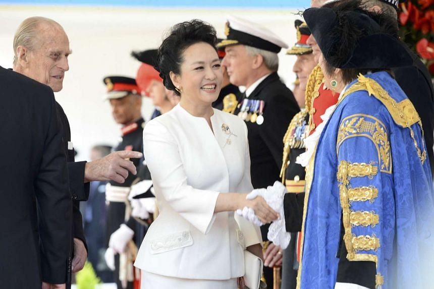 Peng Liyuan, wife of China's President Xi Jinping, greets dignitaries as she attends Xi's official welcome ceremony