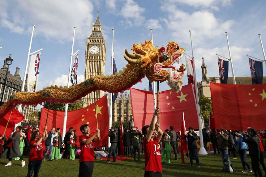 Supporters of China's President Xi Jinping perform opposite Big Ben in Parliament Square ahead of Xi's address to both Houses of Parliament.