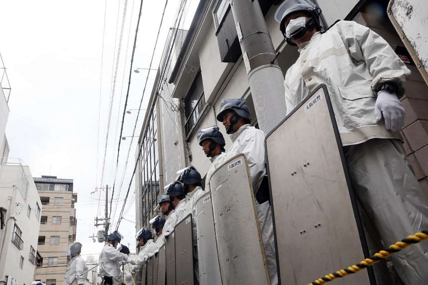 "Japanese riot police stand guard outside of the headquarters of the ""yakuza"" crime syndicate, the ""Yamaken-gumi"", during a police raid on the building in Kobe, on Sept 9, 2015."