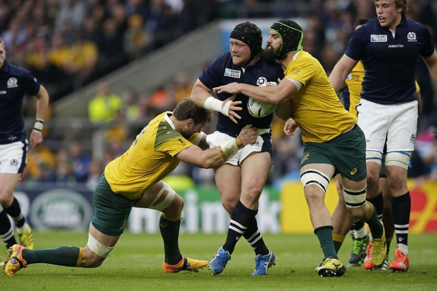Ausralia's Ben McCalman (left) and Scott Fardy (right) tackle Scotland's WP Nel during their Rugby World Cup quarter-final match at Twickenham in London on Oct 18, 2015.