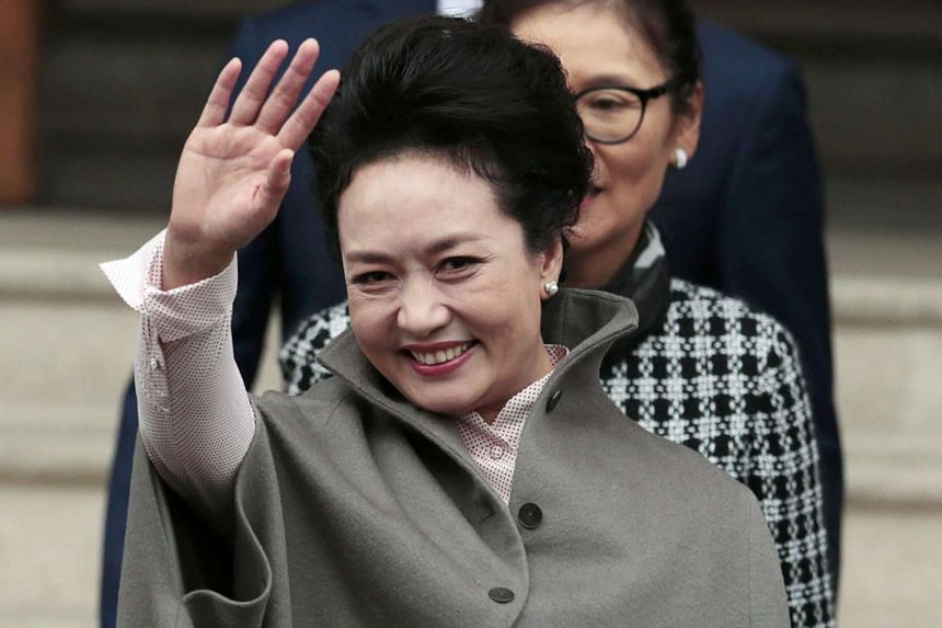 Peng Liyuan, the wife of China's President Xi Jinping, waves as she leaves The Royal College of Music in London, Britain October 22, 2015.