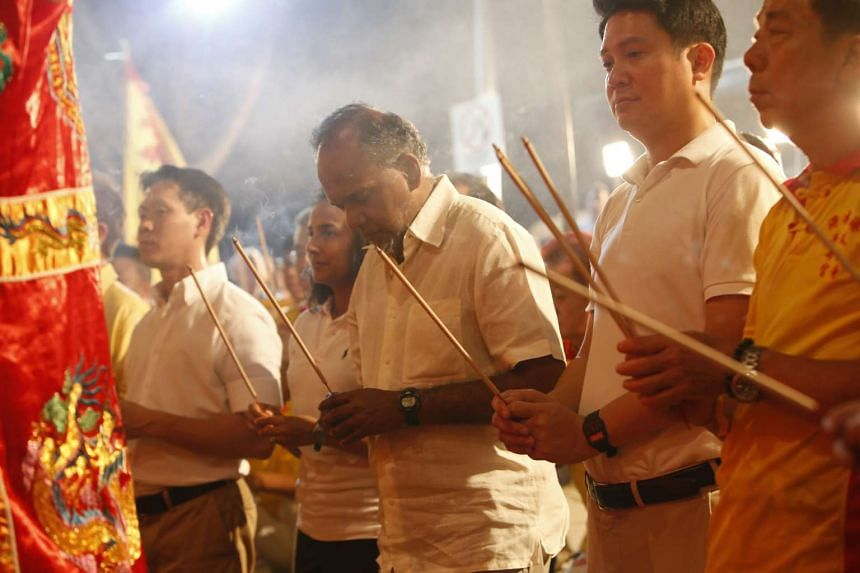 Minister for Home Affairs and Law K. Shanmugam (centre) offering prayers at the Jiu Huang Ye Festival, together with Nee Soon GRC MPs Louis Ng (left) and Henry Kwek (second from right).
