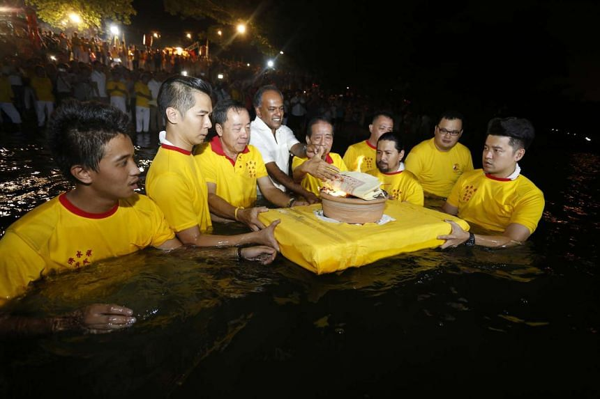 """Minister for Home Affairs and Law K. Shanmugam accompanying temple elders into the waters off Sembawang Beach in a ritual meant to """"send off"""" the Nine Emperor Gods."""