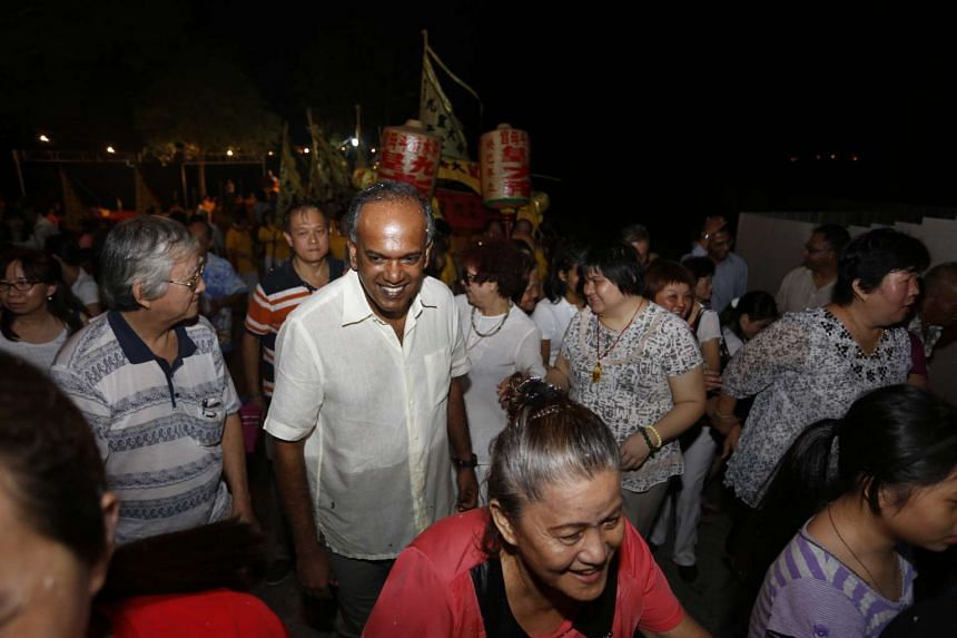 "Minister for Home Affairs and Law K. Shanmugam accompanying temple elders into the waters off Sembawang Beach in a ritual meant to ""send off"" the Nine Emperor Gods."