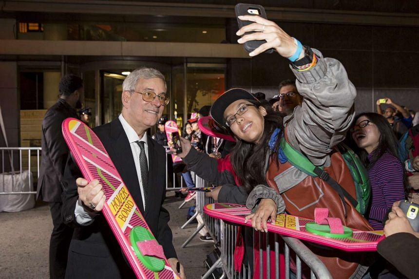 Back to the Future franchise co-creator Bob Gale holding a hoverboard while he greets fans at the film's 30th Anniversary screening in Manhattan on Oct 21, 2015.