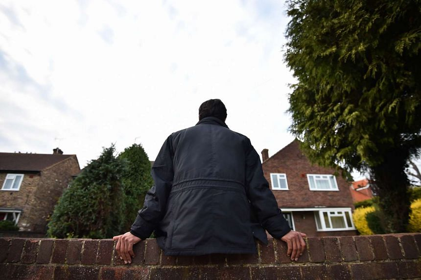 An Iranian asylum seeker sitting on a wall outside his temporary accommodation in Longford, west London, on Oct 15, 2015. An influx of Channel-crossing asylum seekers into a tiny English village has become a tension point in the migration crisis as a