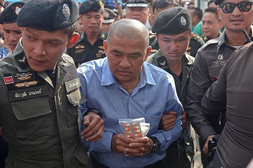 Thai fortune teller Suriyan Sucharitpholwong (centre) arriving at a military court in Bangkok yesterday.