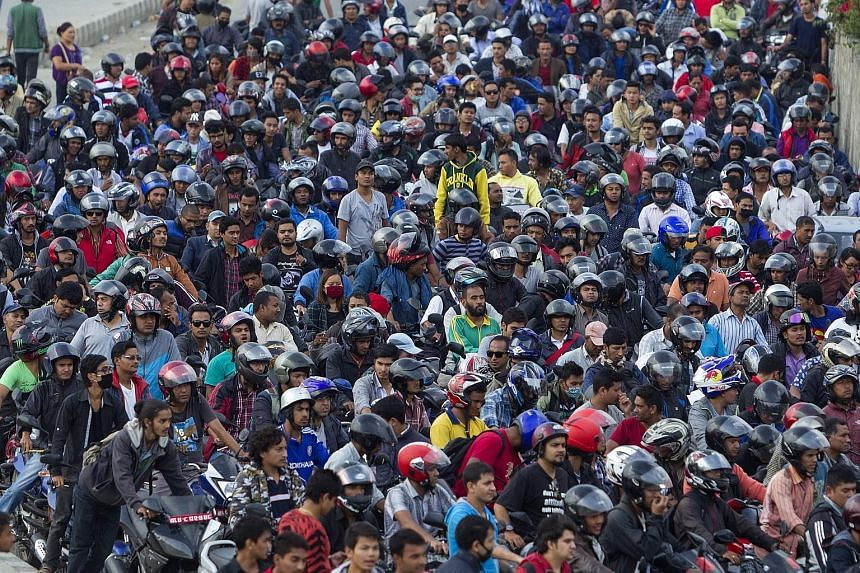 Nepalese pushing their motorcycles as they queue for fuel at a petrol station. A weeks-long blockade of a major border checkpoint by protesters who reject Nepal's new Constitution has sparked a fuel shortage and nationwide rationing, with vital suppl