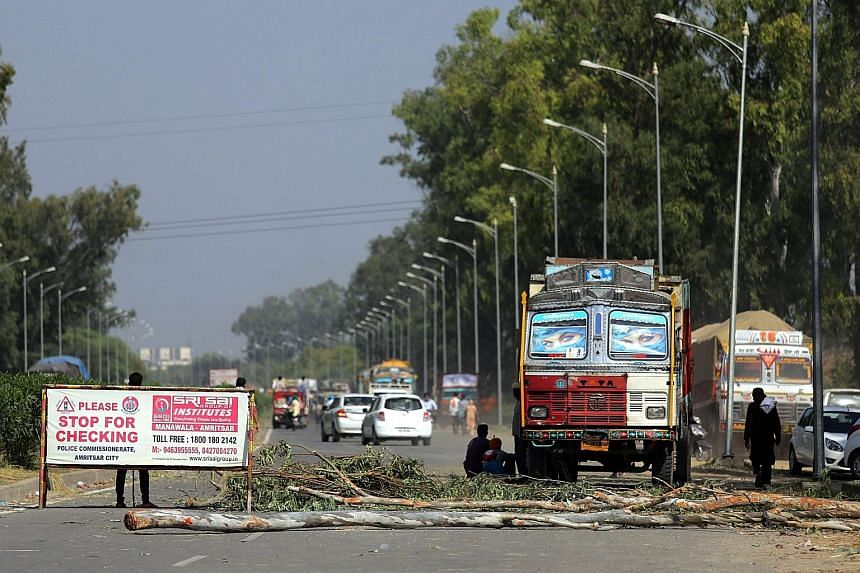 Tree trunks are used as barricades by Sikh activists to block the Amritsar-Delhi National Highway 1, during continuing protests over the desecration of the Sikh holy book.