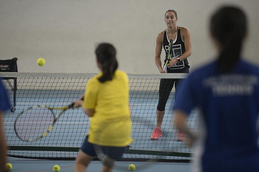 Caroline Garcia (facing camera) hitting a ball during a one-hour tennis cllinic at CHIJ Secondary (Toa Payoh) yesterday.