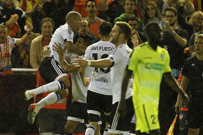 Sofiane Feghouli (left) celebrates after scoring Valencia's first goal in the 2-1 win over Gent. The Spanish side are edging towards the Champions League last 16.