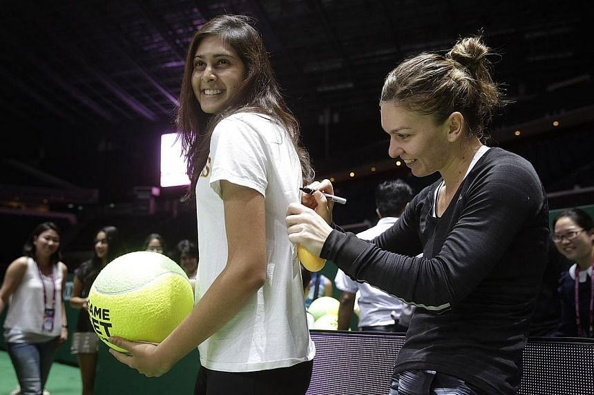 Simona Halep, who beat Serena Williams in the WTA Finals group stage last year, signs a fan's shirt at the Indoor Stadium yesterday.