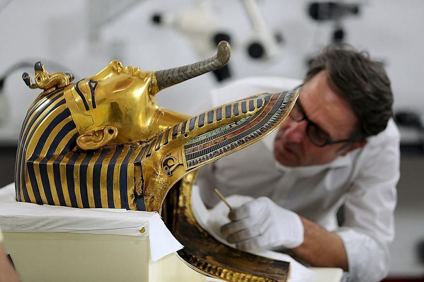 Restoration expert Christian Eckmann working to remove a crust of dried glue from the beard of Tutankhamun's mask in Cairo.