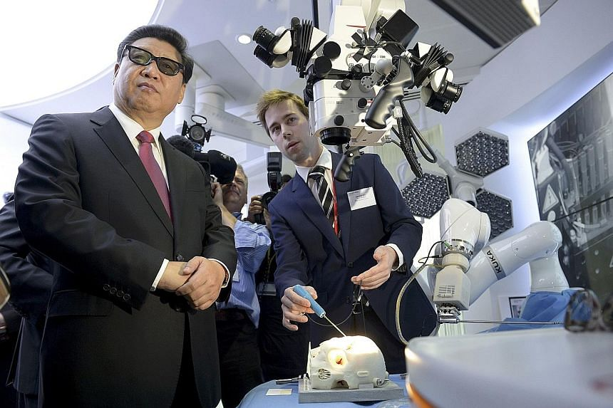 China's President Xi Jinping (left) wears 3D glasses while viewing robotic equipment at the Hamlyn Centre for Medical Robotics, during a visit to Imperial College in London on Wednesday.
