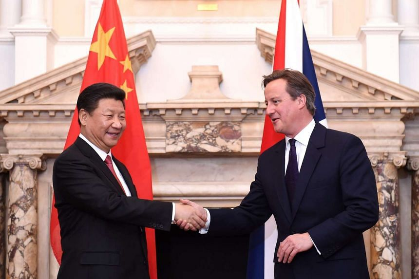 Britain's Prime Minister, David Cameron (right) shakes hand with Chinese President Xi Jinping during the UK-China Business Summit on Oct 21, 2015.