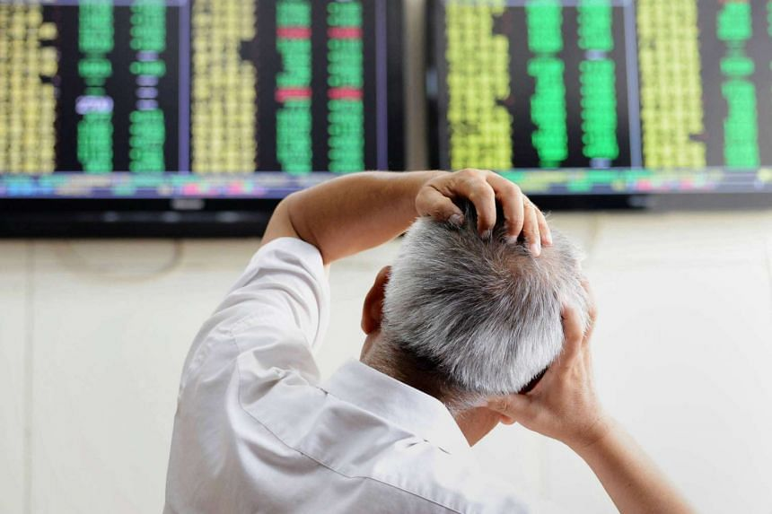 An investor looking at screens showing share prices at a securities firm in Qingdao on Aug 25.