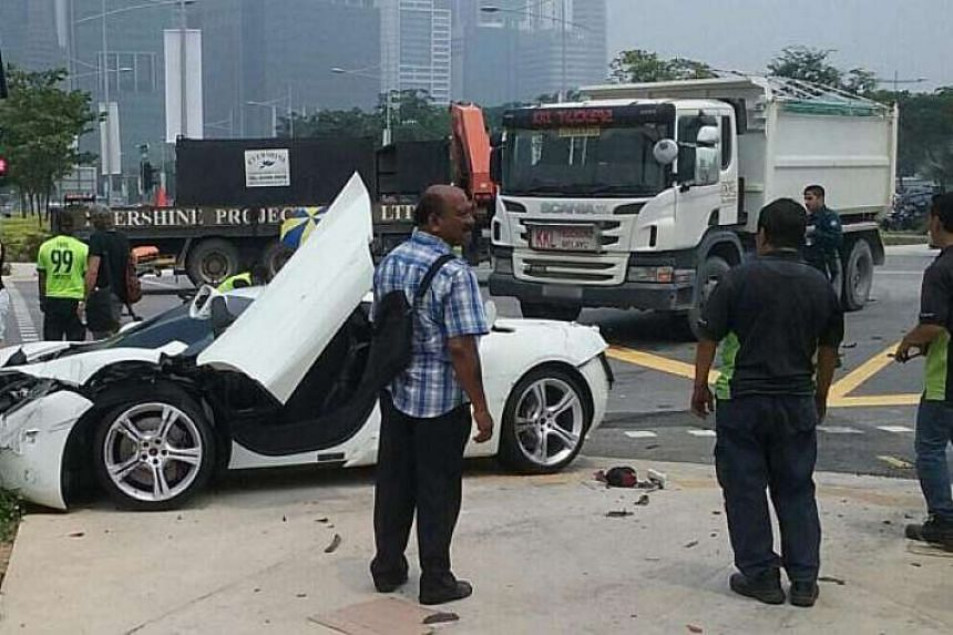 The aftermath of an accident involving a van, a motorcycle and a white sports car at the junction of Marina Boulevard and Bayfront Avenue on Oct 6, 2015.
