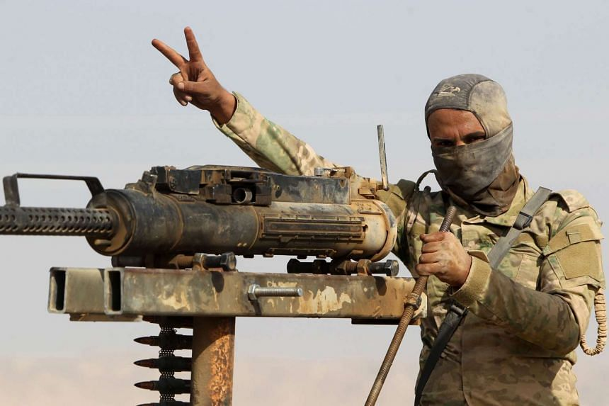 An Iraqi Shi'ite fighter flashes the V for victory sign in the town of Baiji during fighting against ISIS on Oct 16, 2015.