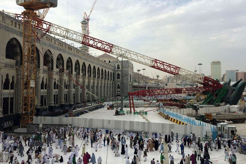 Muslim pilgrims walking past the crane that collapsed at the Grand Mosque in Mecca, Saudi Arabia, on Sept 12, 2015.