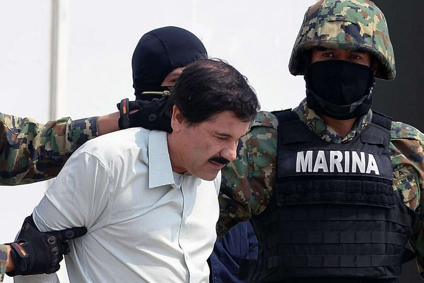 "Mexican drug trafficker Joaquin Guzman Loera aka ""El Chapo"" Guzman, is escorted by marines as he is presented to the press on Feb 22, 2014 in Mexico City."