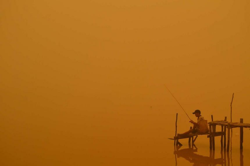 A resident fishes by the river in Palangkaraya city, one of worst-hit by haze, in central Kalimantan province, on Oct 21, 2015.