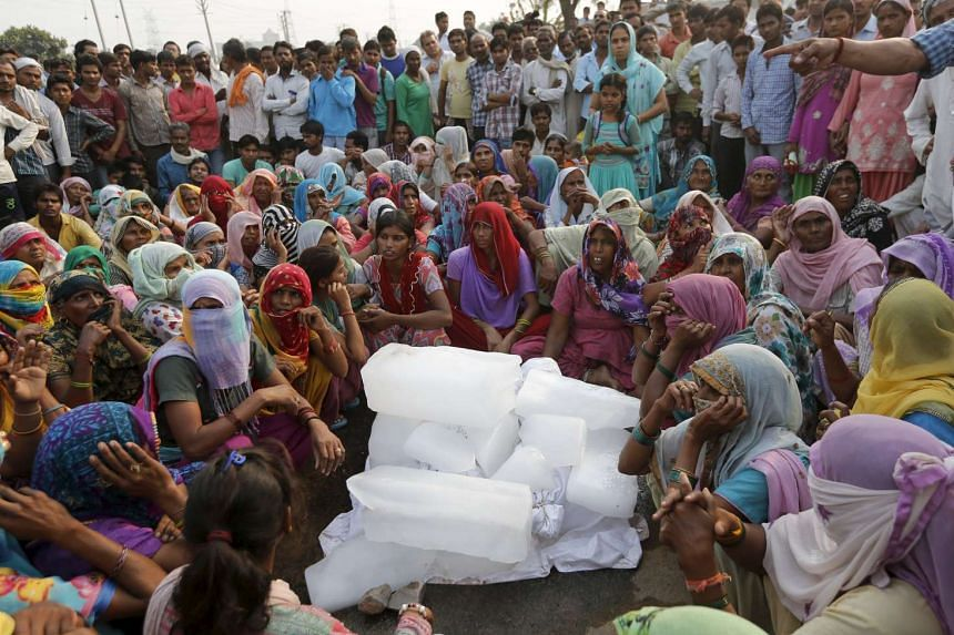 Relatives and villagers mourn as they sit next to the bodies of two children, wrapped in white shrouds, who were burned to death, in Ballabhgarh in the northern state of Haryana, India, on Oct 21, 2015.
