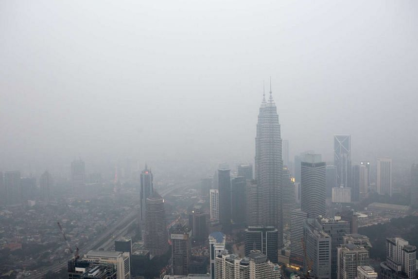 The Petronas Twin Towers and other buildings stand shrouded in haze in Kuala Lumpur, Malaysia, on Oct 19, 2015.