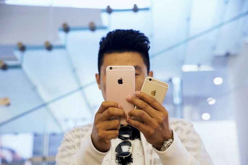 A man takes pictures with an Apple iPhone 6s  in Beijing, China.