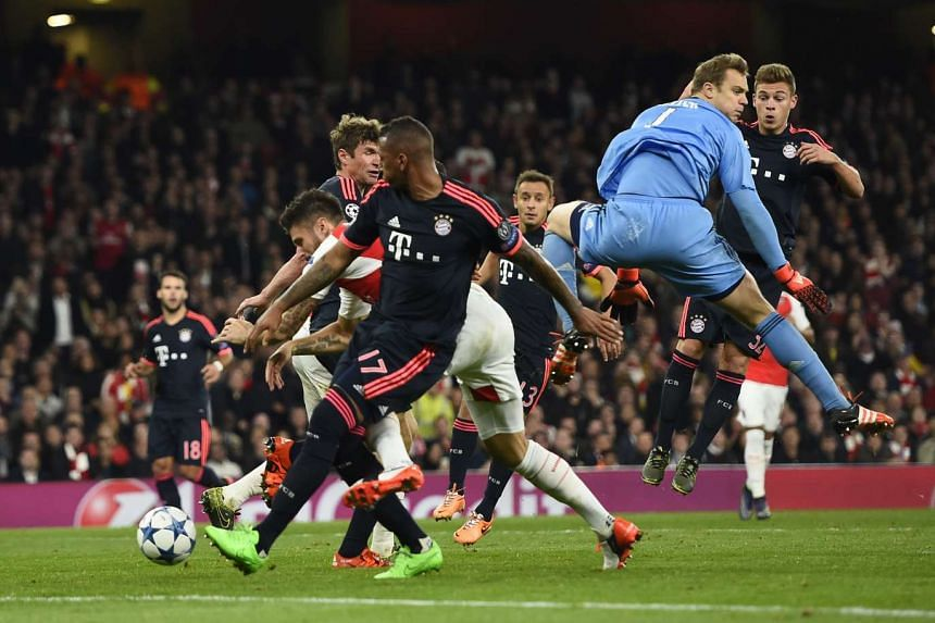 Olivier Giroud (obscured) heading in Arsenal's first goal as Bayern 'keeper Manuel Neuer (in blue) misses the ball, which appeared to brush Giroud's hand.