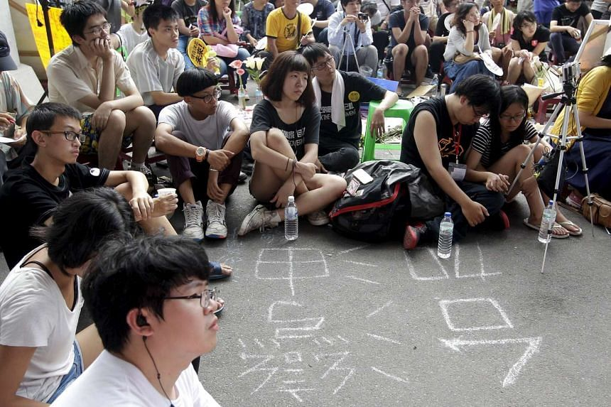 Protesters watch the live broadcast of the meeting between Taiwan's Education Minister Wu Se-hwa and student representatives during a protest in front of the Ministry of Education in Taipei, Taiwan, on Aug 3, 2015.