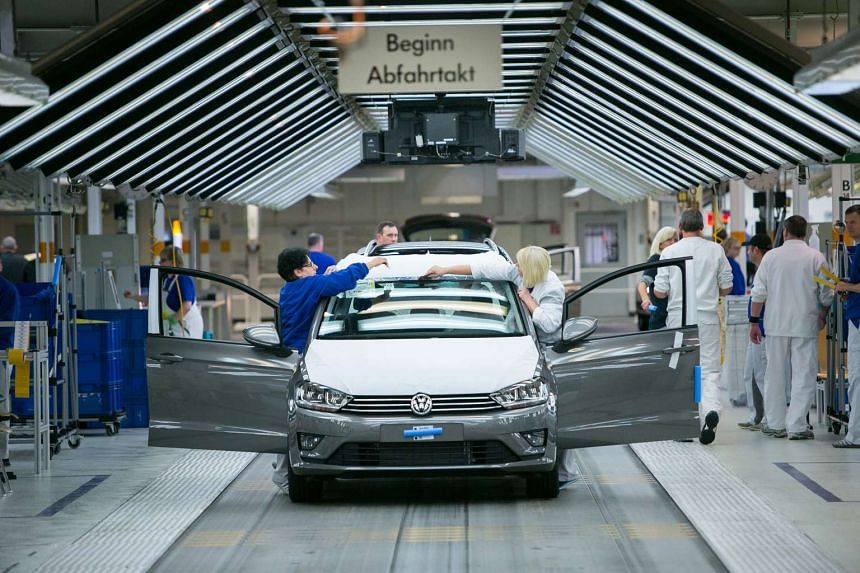 Employees secure protective covers to a Volkswagen Golf automobile following final quality checks on the production line at the Volkswagen AG factory in Wolfsburg, Germany, on Oct 21, 2015.