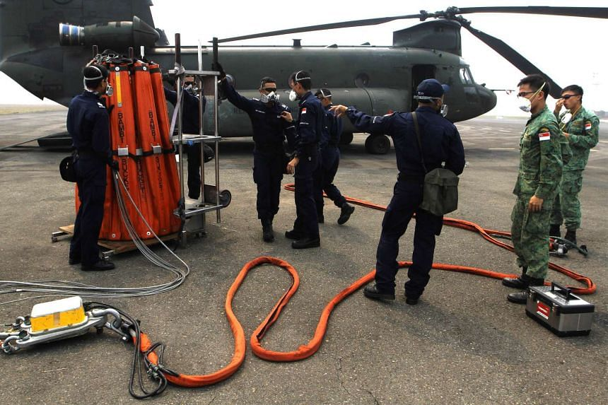 Singapore military and civil defence personnel prepare water bombing equipment beside a SAF chinook helicopter at an Indonesian air base in Palembang on Oct 12, 2015.