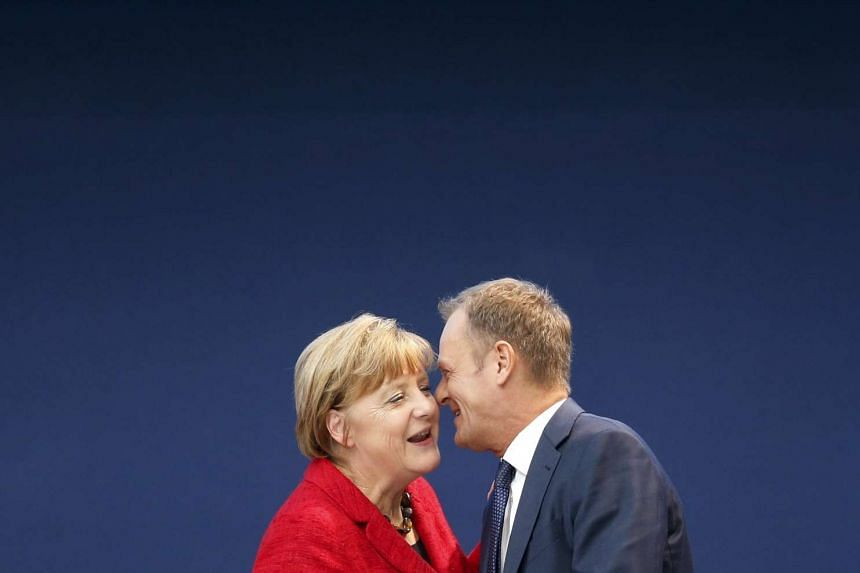 European Council President Donald Tusk (right) greets German Chancellor Angela Merkel during the European People's Party (EPP) congress in Madrid, Spain, on Oct 22, 2015.