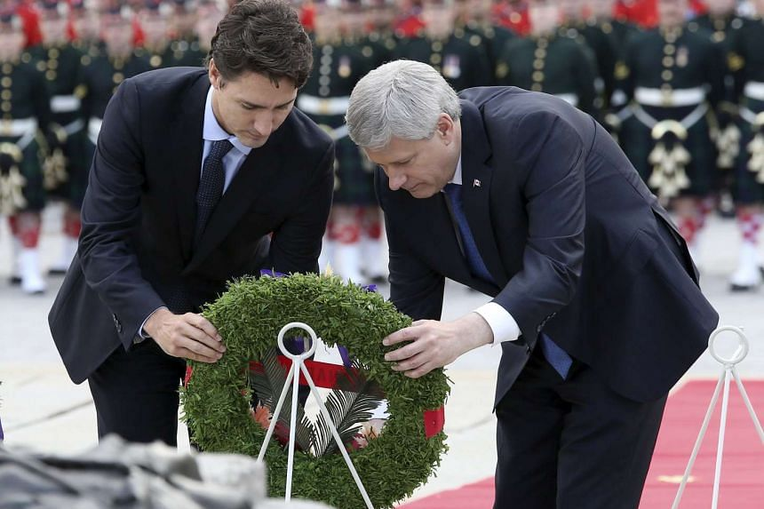 Canada's Prime Minister Stephen Harper (right) and Prime Minister-designate Justin Trudeau lay a wreath during a ceremony to commemorate the Oct 2014 attack on Parliament Hill, at the National War Memorial in Ottawa, Canada on Oct 22, 2015.