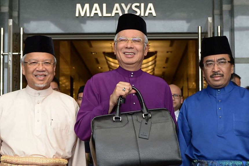 Prime Minister Najib Razak holds a briefcase with second Finance Minister Ahmad Husni Hanadzlah (Left) and Deputy Finance Minister Johari Abdul Ghani before he leaves the Finance Ministry.